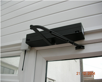 A domestic automatic door opener mounted above a PVCU door with an articulated opening arm which will push the door out to open. & See A Large Range Of Automatic Door Openers